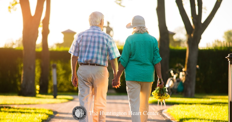 Older couple holding hands and walking together on a path