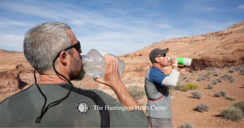 Two men on dessert hike hydrate by drinking water from bottles to keep their bodies and heart health in good condition. The Huntington Heart Center logo at bottom center.