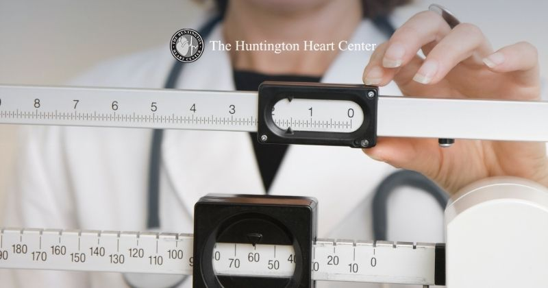 Cardiologist checks patient's weight to determine BMI and related cardiovascular risk factors. Huntington Heart Center logo at top center.