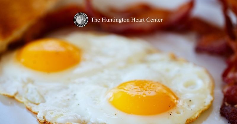 Bacon and eggs on plate show examples of healthy and unhealthy cholesterol in our diet. Huntington Heart Center logo at top center.